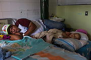2016/05/29 - Barcelona, Venezuela: Jhonatan Diaz sleeps next to his 1 year son, Josué Diaz in a shared room of the children wing at Hospital Dr. Luis Razetti in the Venezuelan city of Barcelona. (Eduardo Leal)