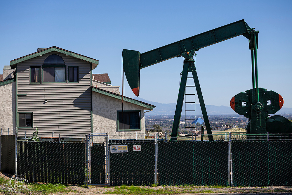 Oil well and pumpjacks in the City of Signal Hill. Once a massive oil producing area, oil wells are still mixed in its now residential neighborhoods. Los Angeles Coutny, California, USA