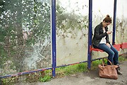 Woman checking her smartphone while waiting at Theale railway station in Berkshire, UK. The waiting area is overgrown with plants and broken glass.