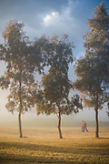 a couple walking in the early morning mist on a golf course in Mesquite, NV.