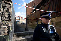 © licensed to London News Pictures. London, UK 19/02/2012. A police officer is waiting on Rosina Street in Hackney, London after a multiple shooting injured five people this morning (19/02/12). Photo credit: Tolga Akmen/LNP