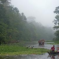 Yanayacu Indians paddle a canoe past a boat carrying tourists on the Yanayacu River in Peru's Amazon Jungle.