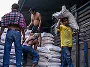 """19 OCTOBER 2012 - BANGKOK, THAILAND:   Workers unload a truck full of sugar in Tha Tien Market in Bangkok. Tha Tien Market is in the middle of """"old"""" Bangkok, near major attractions like the Palace and Wat Po and is in the oldest European style buildings in Bangkok, but most tourists bypass it in favor of the better known attractions.      PHOTO BY JACK KURTZ"""