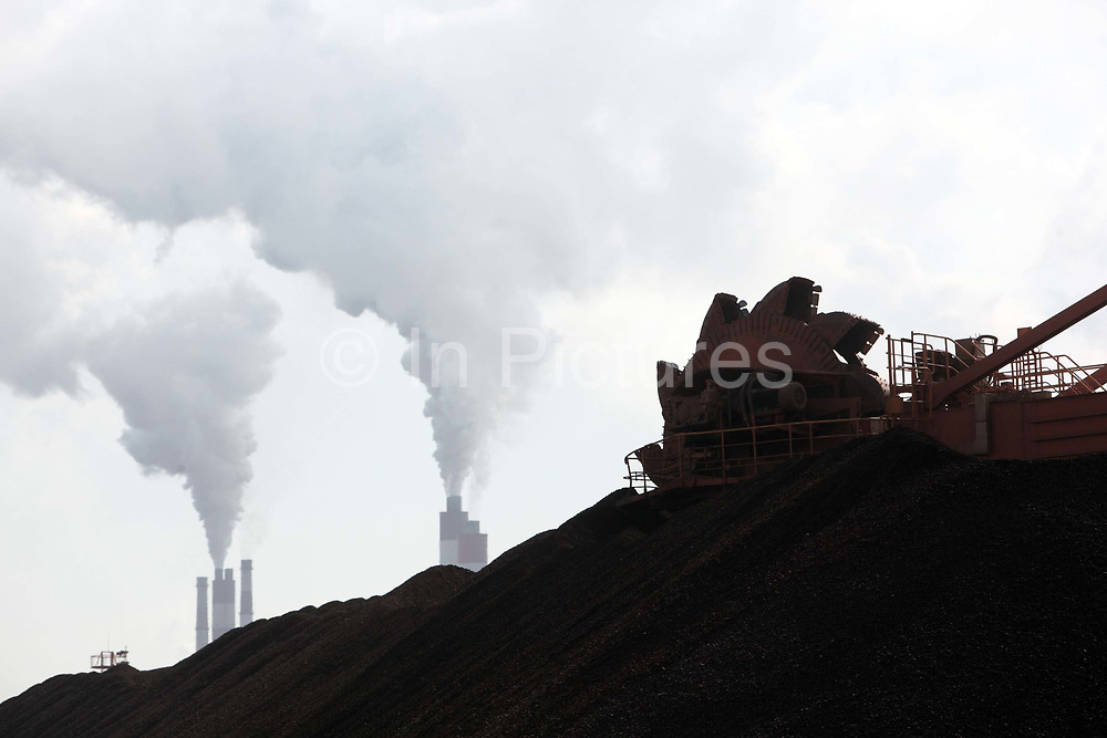 Exhaust rises up from the Chimneys of a large power plant as a mechanical scoop works to dig up and unload a pile of coal in Shanghai, China on 26 January 2010. China's economic boom and hunger for natural resources has been a blessing for countries such as Australia and Brazil, who controls most the world's high quality iron ore deposits.