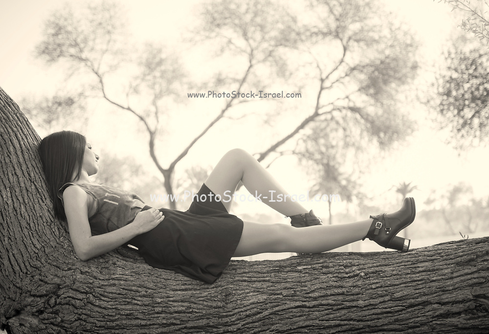 Young middle eastern woman relaxes on a tree trunk in a park
