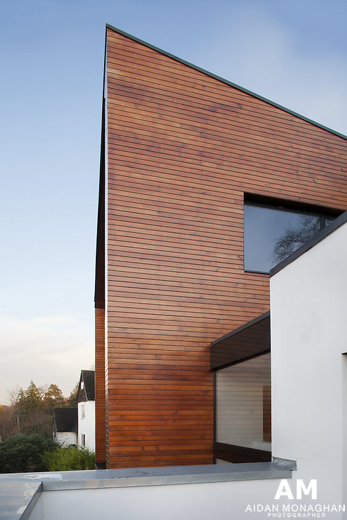 Architecture Photography Belfast, Architecture Photography Northern Ireland<br /> <br /> Building: 007 House <br /> <br /> Location: Holywood, <br /> County Down<br /> <br /> Architect: BGA Ltd.<br /> <br /> Building Type:Private House<br /> <br /> Architects Description: <br /> <br /> It is said the most important part in designing and building your own home is the relationship between the client and the architect. With BGA this relationship couldn't have gone better. <br />  <br /> Capturing the original brief, understanding the clients and developing concepts to arrive at that magical combination between originality, great context to the surroundings, practicality, ease of construction and excitement that only great design has, is what BGA excelled at in this project. <br />  <br /> The design concept of an eye looking out of the hillside over the lough is what made sense to the site. Making that eye out of light materials, sympathethic to the wooded context and then rooting that solidly into the hillside with the lower concrete structure developed that concept to perfection. Internally, the house is designed to be practical, liveable in by a family rather than just a showhouse. Importantly also, the upper, living areas also connect seamlessly to the outside spaces thanks to the extensive glazing. <br />  <br /> Being able then to translate that design with the aid of their selected structural engineer into a detailed construction plan and then guiding us through the tender and later the build process, we found John and everyone at BGA a pleasure to work with. Arguably it was in the build phase that BGA proved their greatest value. The fact that it mattered to them to create and finish what we have now is what sets them apart from other architects.<br /> <br /> Architecture Photography Belfast, Architecture Photography Northern Ireland, architecture architectural interior exterior photography Belfast, architectural photographer Belfast, architecture photographer 