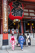 Japanese women dressed in kimono, enter the main hall of the Sensoji Buddhist temple in Asakusa, Tokyo, Japan. The temple was built during the Kamakura period in 645 CE and is the oldest and most important temple in Tokyo.