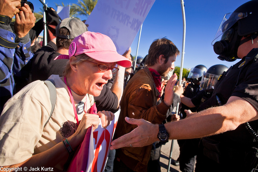 30 NOVEMBER 2011 - PHOENIX, AZ:    An anti-ALEC protester confronts a line of police at the Westin Kierland Resort and Spa Wednesday. About 300 people picketed the American Legislative Exchange Council (ALEC) conference at the Westin Kierland Resort and Spa in Phoenix, AZ, Wednesday. The protesters claim ALEC, a conservative think tank, violates its tax exempt status by engaging in lobbying, a charge ALEC officials deny. Many conservative pieces of legislation, like Arizona's anti-immigration bill SB1070, originate with ALEC conferences (SB 1070 originated at an ALEC conference several years ago). Many of the protesters are also members of the Occupy movement.  PHOTO BY JACK KURTZ