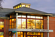 Merrick, New York, USA. January 24, 2019. During winter sunset, golden reflection of trees and building fills windows of Merrick Public Library on south shore of Long Island.
