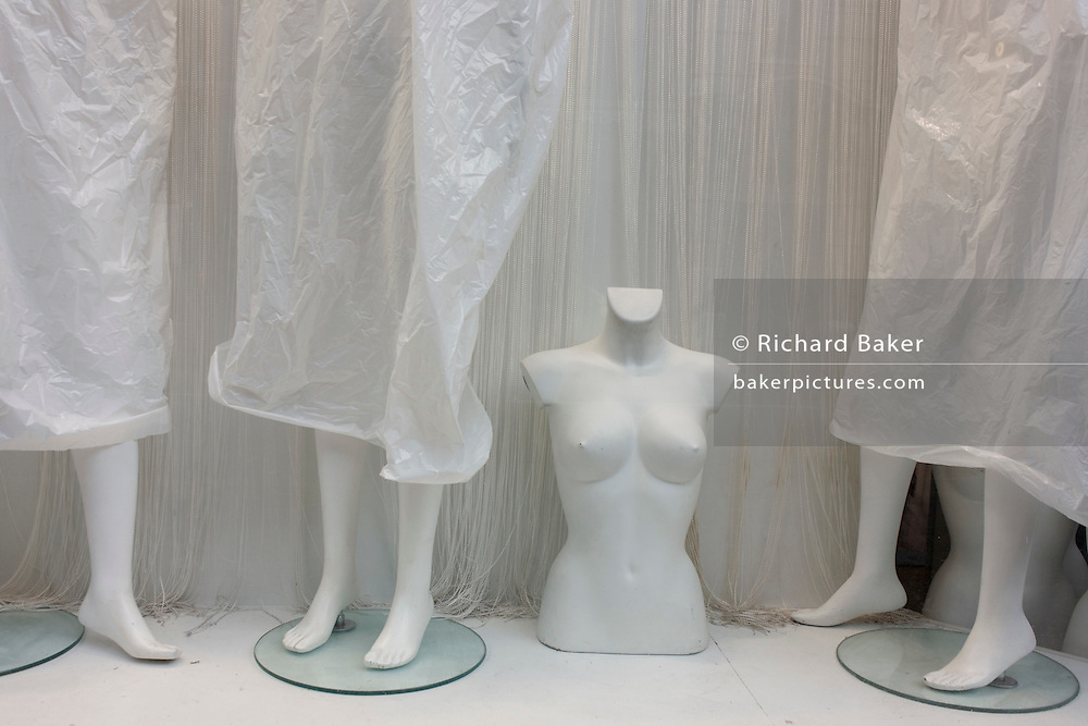 Covered mannequins, awaiting clothing in a London retail shop woindow.