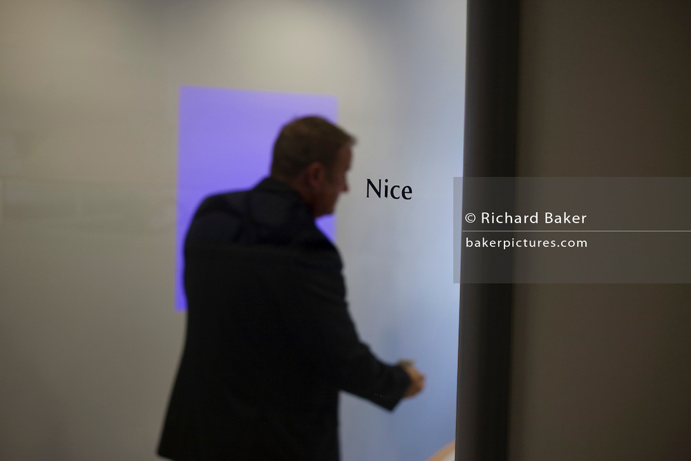 "After an internal meeting, a male employee is ready to leave a small conference room at the British Airways' corporate headquarters at Waterside at Harmondsworth near Heathrow Airport. Themed rooms like this are titled after BA's destinations - in this case, the southern French Cote d'Azur town of Nice. The man is reaching out to shake a colleague's hand before they all exit and re-convene elsewhere. Focus is on the room's name and not on the man, who remains anonymous. From writer Alain de Botton's book project ""A Week at the Airport: A Heathrow Diary"" (2009). ."