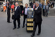 Passers-by and a mobile rack of Jehova's Witness pamphlets outside Liverpool Street station, City of London. Such racks seem to be everywhere around the capital, at major junctions and stations where the public might be persuaded to take a leaflet and learn about this religious group. Three men pass the dispenser without noticing its contents, eager to continue their onward journeys from this mainline station.
