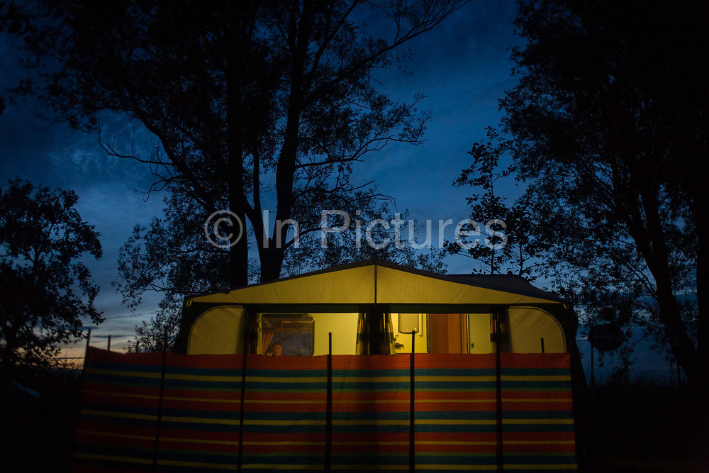 Nightfall on trees and the campsite in Reedham on the Norfolk Broads. A lone caravan with its owner watching TV, a striped windbreak and a glow from awning lights looks forlorn but peaceful at this tranquil place. The last daylight fades behind after another fine summer's day at this popular location in East Anglia know for its flat landscape and wide skies.