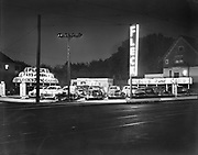 ackroyd_00138-1. Night shot of Fleck's Used Car Lot, 2811 NE Union, corner of Graham. (Now 2811 Northeast Martin Luther King Junior Boulevard) on the lot is now a brand new store and office building, old house next door is still there. September 11, 1947