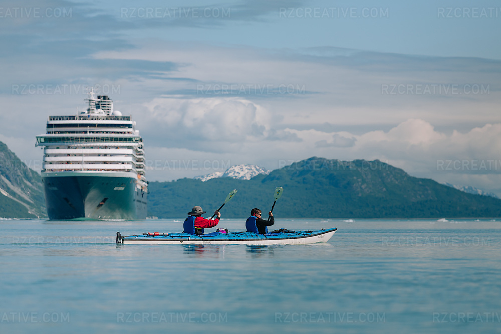A couple paddle a tandem kayak with a cruise ship in the distance in southeast Alaska's Glacier Bay National Park and Preserve. Photo © Robert Zaleski / rzcreative.com<br /> —<br /> To license this image contact: robert@rzcreative.com
