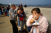 On a crowded spring day at the seaside, when families and holidaymakers, daytrippers and locals gather at England's coastal regions, a woman here is seen biting into a very soft cream cake. Covered with a chocolate topping, she sinks her mouth into its pastry and somehow manages not to let the cream ooze out over her clothes. Holding a serviette to catch drips, she looks elsewhere as behind, others stand or lean against the solid concrete sea defence wall at Scarborough, North Yorskhire.