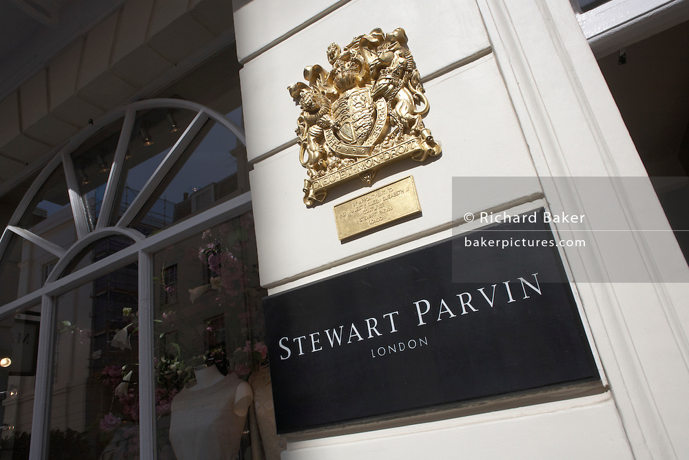 With a prominent Royal Warrant as couturier to Her Majesty the Queen, the fashion house Stewart Parvin's boutique name is seen outside 14 Motcomb Street in exclusive Belgravia, London. Royal Warrants are a mark of recognition to individuals or companies who have supplied goods or services for at least five years to HM The Queen, HRH The Duke of Edinburgh or HRH The Prince of Wales. There are around 850 Royal Warrant Holders representing a huge cross-section of trade and industry. Warrant Holders may display the relevant Royal Arms and the legend 'By Appointment' on their products, premises, stationery, vehicles and advertising but must adhere to strict guidelines for its proper use......Motcomb Street SW1