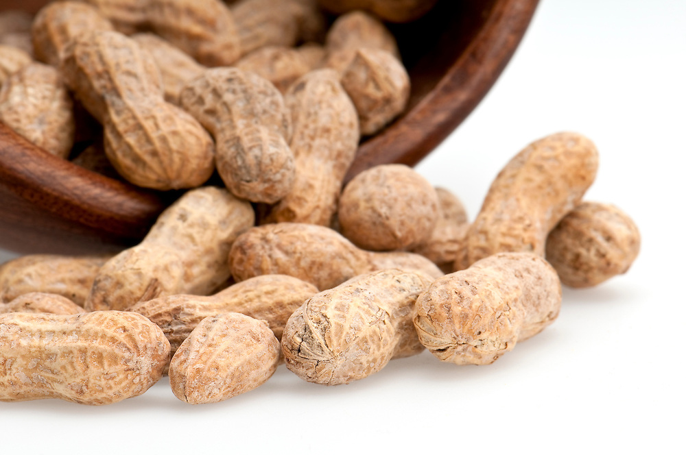 Close up view of peanuts spill from bowl, macro shot, use of selective focus.