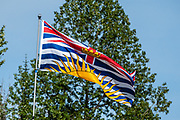 The flag of British Columbia is based upon the shield of the provincial arms of British Columbia. At the top of the flag is the Royal Union Flag centered by a crown. The setting sun represents BC's location in western Canada. The four wavy white and three wavy blue lines symbolize being located between the Rocky Mountains and the Pacific Ocean.  Photo is from Meziadin Lake Provincial Park, in British Columbia, Canada. It sits 40 miles (64 km) east of Stewart; inland from Bear Pass. A beautiful mountain lake, surrounded by forest, it is also defined to the west by a ridge a tall mountains of the Coast Range. The scenic Stewart–Cassiar Highway (Highway 37, aka Dease Lake Highway or Stikine Highway) is the northwesternmost highway in BC.