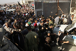 Palestinians rush the Mukataa, the headquarters of the Palestinian National Authority, to get a glimpse of Yasser Arafat as he is buried in the compound, Ramallah, Palestinian Territories, Nov. 12, 2004. Arafat died in a Paris hospital at the age of 75.