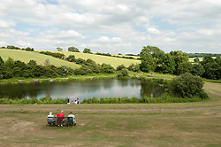 A child and adults watch children fishing, Grimethorpe, South Yorkshire