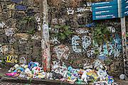 Trash piles up along a street along a graffiti wall in the Santa Teresa neighborhood in Rio de Janeiro, Brazil.