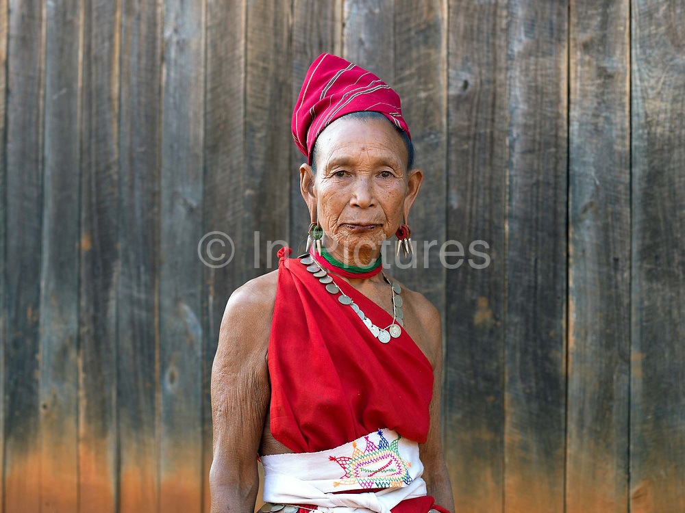 Portrait of a Kayah Red Karen ethnic minority woman on 18th January 2016 in Kayah State, Myanmar. Myanmar is one of the most ethnically diverse countries in Southeast Asia with 135 different indigenous ethnic groups with over a dozen ethnic Karenni subgroups in the Kayah region. Kayah women wear a simple red tunic worn with a broad white sash decorated with coloured tassles and a striped hand-woven head-cloth