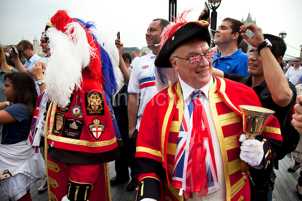 London, UK. Friday 27th July 2012. The London 2012 Olympic Games torch makes it's way up the River Thames on the final day of the torch relay. On the banks of the river crowds gather in celebration, including this town crier.