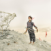 """Young pilgrims. The steep trek to the rim of the highest volcano is the first ritual of the Hinglaj pilgrimage. Pilgrims come up to throw a coconut in the cold mud (to thank the gods for granting their wish) and to apply the holy volcanic mud to their faces etc. The area around Chandragup (meaning """"Moon Well""""), a sacred site to Hindu of 3 mud volcanoes (mainland Asia's largest ones)."""