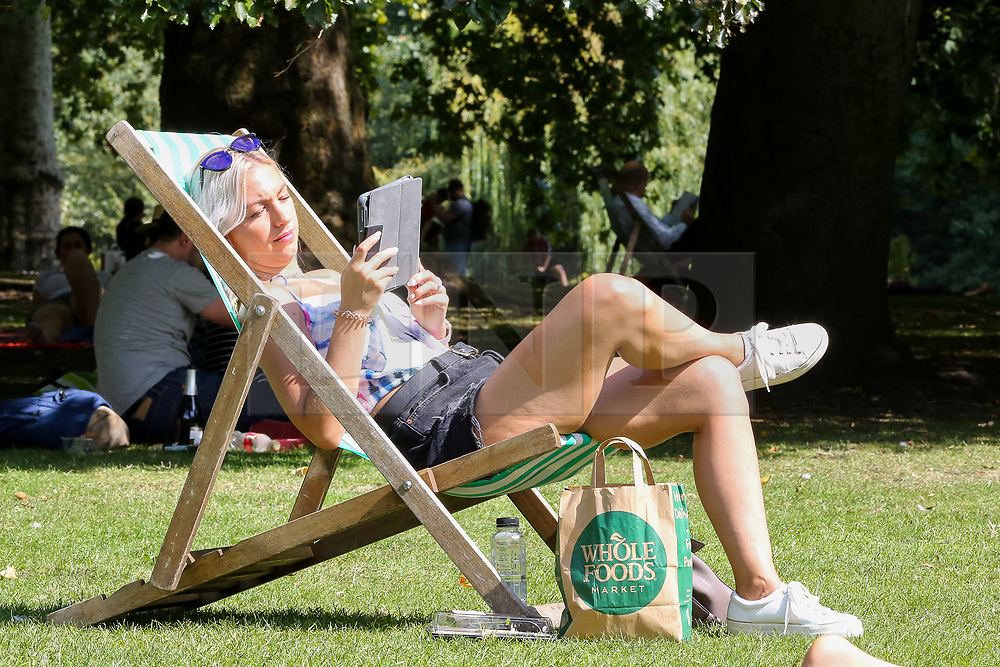 © Licensed to London News Pictures. 24/08/2019. London, UK. A woman sitting in a deckchair in London's St James's Park as the hot weather continues. According to the Met Office, the temperatures are forecast to reach between 31 and 33 degrees celsius in the south-east of England. <br /> <br /> ***Permission Granted***<br /> <br /> Photo credit: Dinendra Haria/LNP
