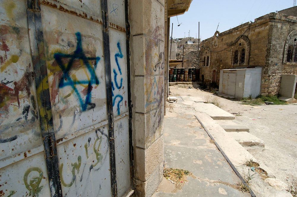 Israeli settler graffiti in Hebron. Some 400 Israeli settlers, protected by 5,000 Israeli soldiers, have used intimidation and violence to drive Palestinian shopkeepers from the center of the ancient city of Hebron, in the southern part of the West Bank. Many businesses have closed and their owners have moved away. Many claim that is the ultimate goal of the settlers, who believe that they have a divine right to the land around Hebron.