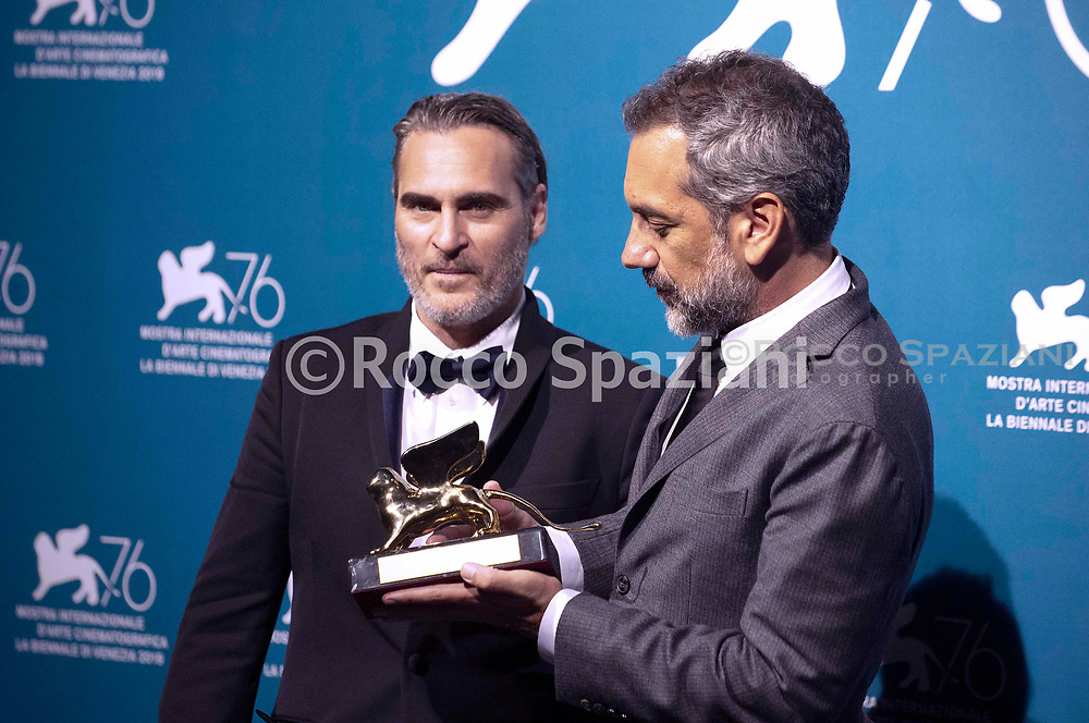 """US director Todd Phillips (R), flanked by US actor Joaquin Phoenix, holds the Golden Lion award for Best Film he received for the movie """"Joker"""" during the awards ceremony winners photocall of the 76th Venice Film Festival on September 7, 2019 at Venice Lido."""
