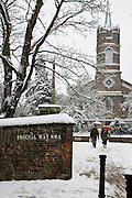 Two people walk by St John At Hampstead Parish Church and graveyard, North London, UK