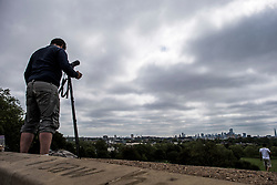 © Licensed to London News Pictures. 10/06/2021. London, UK. An astronomy enthusiast watches from Primrose Hill in north London as clouds obstruct a partial solar eclipse. Viewers in the UK will witness a crescent sun during the lunar spectacle, as as the moon passes between the Earth and the sun. Photo credit: Ben Cawthra/LNP