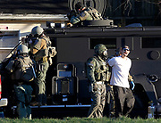 The suspected bank robber calls out to his neighbors at Friendship Court as he is arrested by police without incident outside of 504 Sixth Street Southeast after a multi-hour stand off Tuesday afternoon in Charlottesville, Va. Photo/The Daily Progress/Andrew Shurtleff