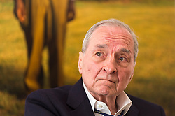 """© Licensed to London News Pictures. 10/04/2019. LONDON, UK.  American photographer William Eggleston poses in front of one of his works from his new exhibition """"2¼"""" at the David Zwirner gallery in Mayfair.  The show comprises a series of square-format colour photographs taken around 1977 throughout California and the American South and will run April 12 to June 1, 2019. Photo credit: Stephen Chung/LNP"""
