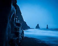 Reynisfjara black sand beach on the south coast of Iceland. Reynisdrangar sea stacs in background. January morning twilight.
