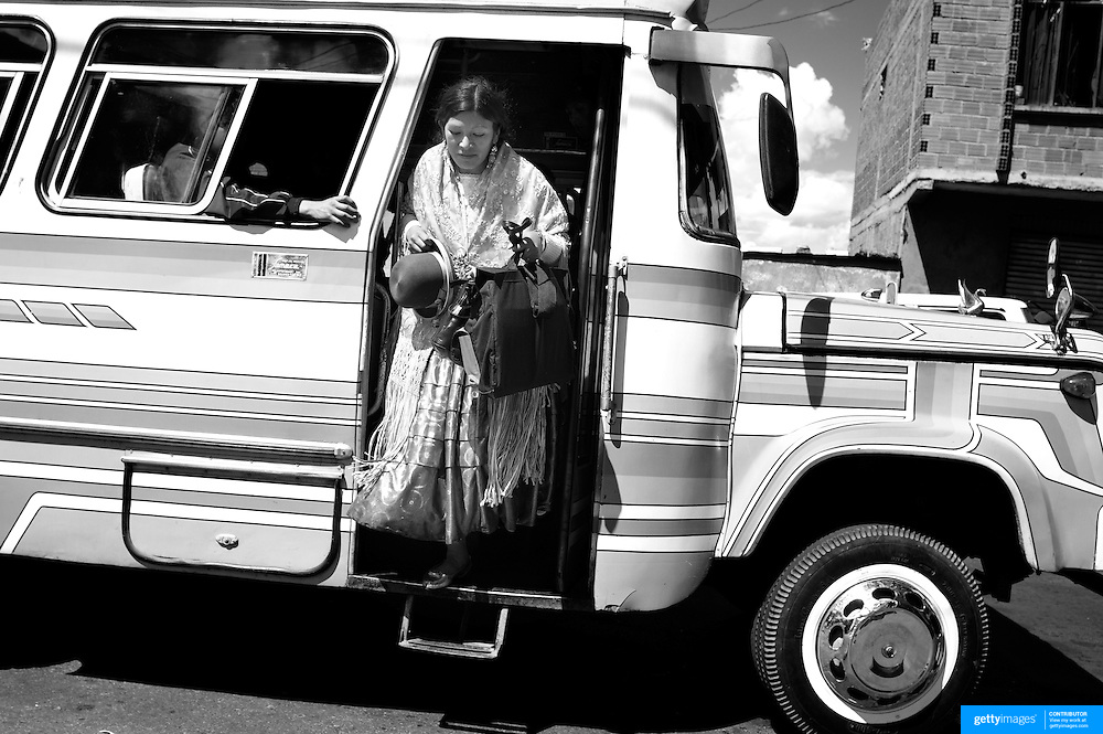 Cholita wrestler Yolanda La Amorosa  gets off the bus with her daughter near their home in La Paz after collecting her from school. Yolanda is part of the 'Titans of the Ring' wrestling group who perform every  Sunday at El Alto's Multifunctional Centre. Bolivia. The wrestling group includes the fighting Cholitas, a group of Indigenous Female Lucha Libra wrestlers who fight the men as well as each other for just a few dollars appearance money. El Alto, Bolivia, 17th March 2010. Photo Tim Clayton