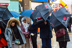 London, December 31 2017. The umbrellas come out as a downpour begins in London's west end ahead of the New Year's Eve fireworks at midnight. PICTURED: Umbrellas catch the wind as it begins to rain in Leicester Square. © SWNS