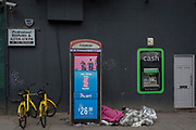 The sleeping bag of a homeless person inside a phone kiosk and next to an ATM cash dispenser operated by Bank Machine on Old Street, aka Silicon Roundabout, 7th March 2018, in London England.