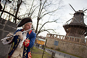 A German man playing the flute and wearing traditional dress outside the windmill in the Sans Souchi Palace complex, Potsdam, Brandenburg, Germany.