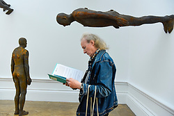 "© Licensed to London News Pictures. 17/09/2019. LONDON, UK. A visitor next to ""Lost Horizon I"", 2008, by Antony Gormley, which comprises 24 cast iron body forms. Preview of a new exhibition by Antony Gormley at the Royal Academy of Arts.  The show bring together existing and specially conceived new works from drawing to sculptures to experimental environments to be displayed in all 13 rooms of the RA's Main Galleries 21 September to 3 December 2019.  Photo credit: Stephen Chung/LNP"