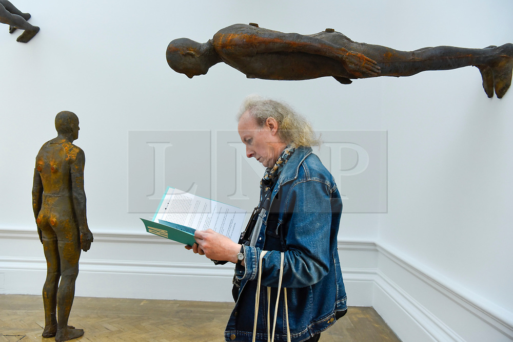 """© Licensed to London News Pictures. 17/09/2019. LONDON, UK. A visitor next to """"Lost Horizon I"""", 2008, by Antony Gormley, which comprises 24 cast iron body forms. Preview of a new exhibition by Antony Gormley at the Royal Academy of Arts.  The show bring together existing and specially conceived new works from drawing to sculptures to experimental environments to be displayed in all 13 rooms of the RA's Main Galleries 21 September to 3 December 2019.  Photo credit: Stephen Chung/LNP"""