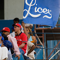 10 january 2006: A fan of Baseball team Licey waives a flag at Estadio Quisqueya, Santo Domingo, Dominican Republic.