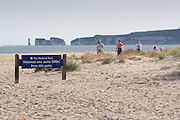 Visitors to Studland Beach pass a sign alerting them to the presence of naturists, Dorset, UK.