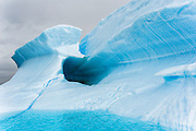 Sculpted iceberg in turquoise colored water, Iceberg Alley, near Pleneau Island, Antarctica