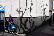 A lady cyclist reads Barclays-sponsored bike rental instructions with shadows of bare branches on white wall. She has been riding a newly rented 'Boris bike' in Westminster, Central London. The sponsored bicycles have been provided for Londoners and visitors by Barclays Bank and is the brainchild of Mayor of London, Boris Johnson whose aim is to cut down on heavy traffic and increase cycling journeys.