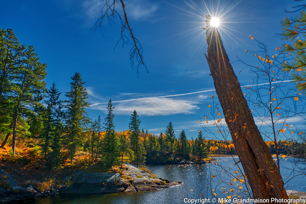 Sunburst behind a stump on Lake of The Woods on Storm Bay Road<br />Kenora<br />Ontario<br />Canada