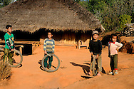 Burma/Myanmar,Golden Triangle. Boys with tires staying in front of the house.