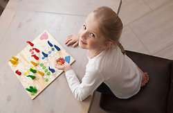 Girl playing board game, Bavaria, Germany